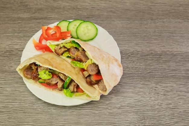Falafel e legumes frescos no pão pita em madeira