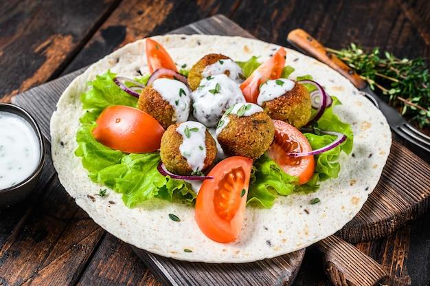 Falafel vegetariano com legumes e molho tzatziki em pão tortilla