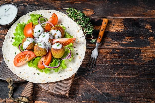 Falafel vegetariano com legumes e molho tzatziki em um pão tortilla. fundo de madeira escuro. vista do topo. copie o espaço.