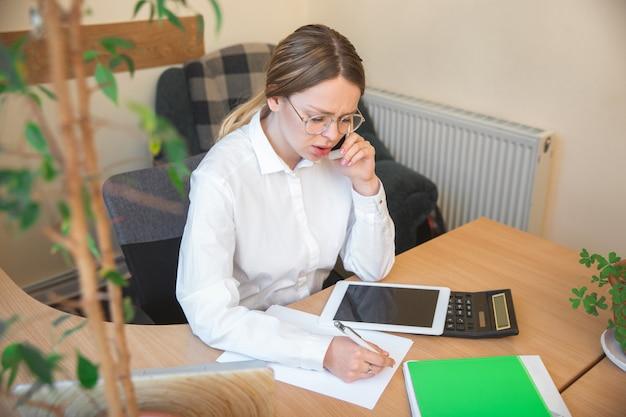 Falando ao telefone. empreendedor caucasiano, mulher de negócios, gerente trabalhando concentrado no escritório. parece serio e ocupado, vestindo um traje clássico. conceito de trabalho, finanças, negócios, sucesso, liderança.