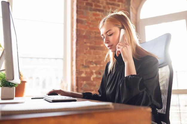 Falando ao telefone. mulher jovem caucasiana em traje de negócios, trabalhando no escritório. jovem empresária, gerente fazendo tarefas com smartphone, laptop, tablet tem conferência online. finanças, trabalho.