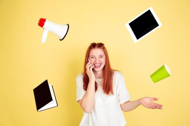Falando ao telefone. retrato de mulher jovem caucasiana em estúdio amarelo