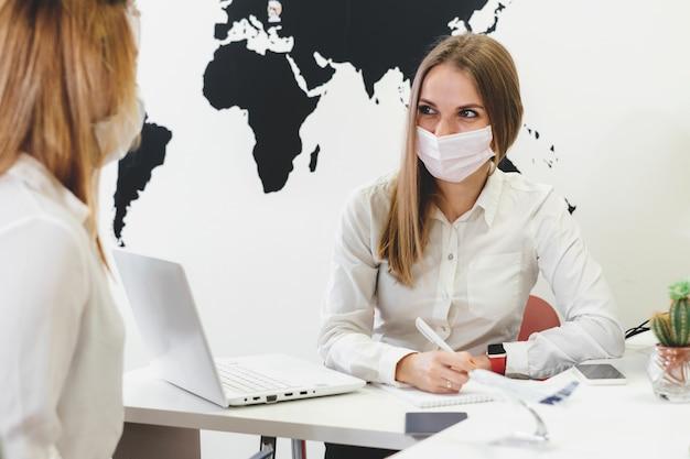 Falando com máscara facial na agência de viagens