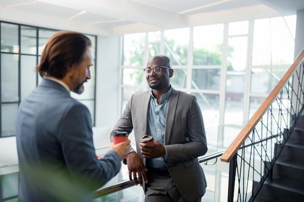 Falando com o colega. homem de negócios barbudo, de pele escura, usando óculos, falando com um colega