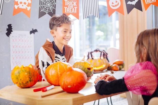 Falando com um amigo. garoto engraçado radiante usando fantasia de esqueleto de halloween conversando com sua linda amiga