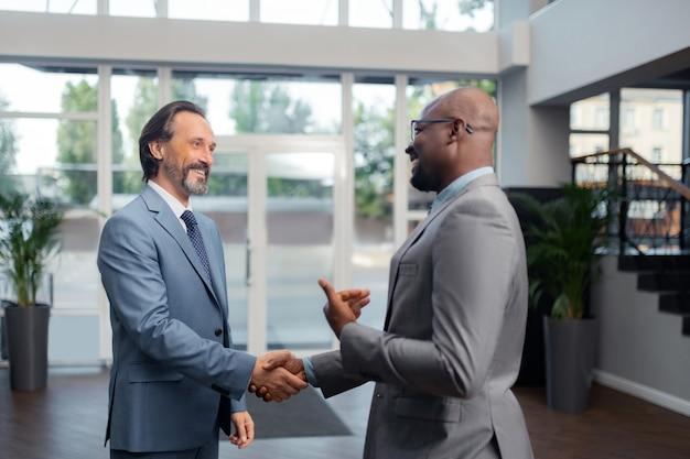 Falando com um colega. homem de negócios grisalho sorrindo enquanto falava com seu colega de escritório