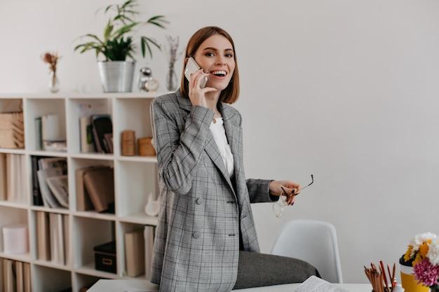 Falando no iphone, a senhora com um sorriso amigável enquanto está sentada no local de trabalho.
