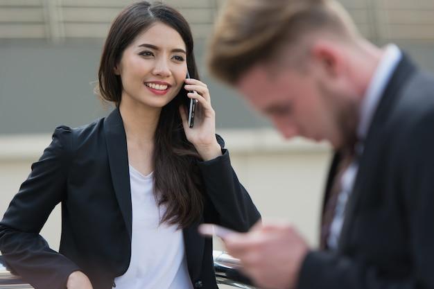 Falando no telefone, sorrindo mulher de negócios, falando no celular, telefone celular na mão.