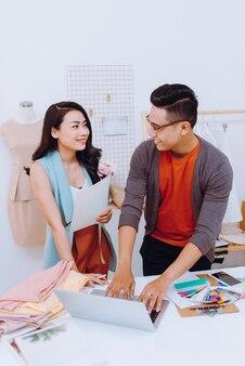 Falando sobre novo design de moda. mulher jovem e bonita conversando com o parceiro enquanto trabalham juntos na oficina
