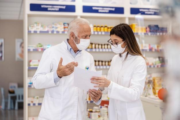 Falando sobre trabalho em uma farmácia. colegas olham para o papel prescrito e discutem