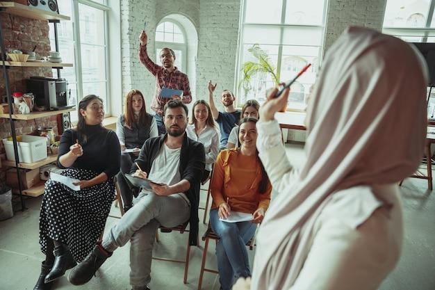 Falante muçulmana feminina, fazendo uma apresentação no corredor do workshop. audiência ou sala de conferências. perguntar aos participantes na audiência. evento de conferência, treinamento. educação, diversidade, conceito inclusivo.