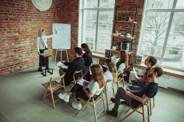 Falante muçulmana feminina, fazendo uma apresentação no corredor do workshop. audiência ou salão. visão de alto ângulo dos participantes na audiência. evento de conferência, treinamento. educação, diversidade, conceito inclusivo.