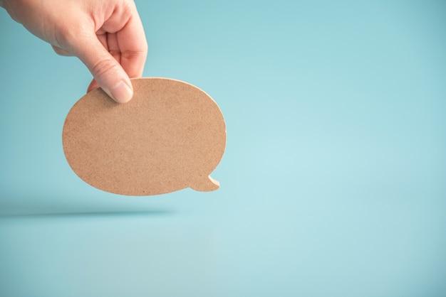 Falar com o ícone do discurso de bolha. mão segurando as bolhas em branco vazias elementos de design em azul