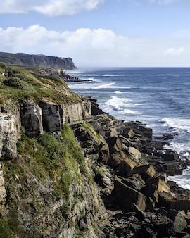 Falésia junto ao mar com o cabo da roca à superfície
