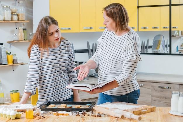 Falha de cozimento. mãe ensinando filha a fazer biscoitos, segurando o livro de receitas, apontando o erro.