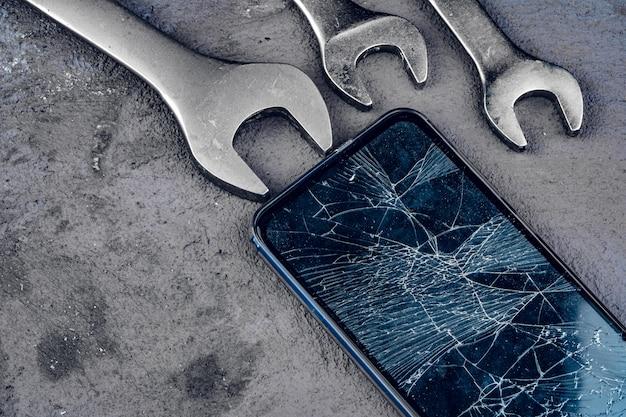 Falha no smartphone com ferramentas de reparação na parede cinza