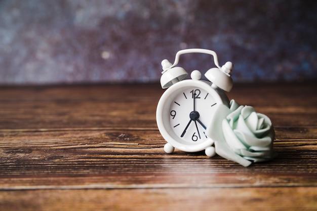 Falsa rosa branca com despertador em fundo de madeira