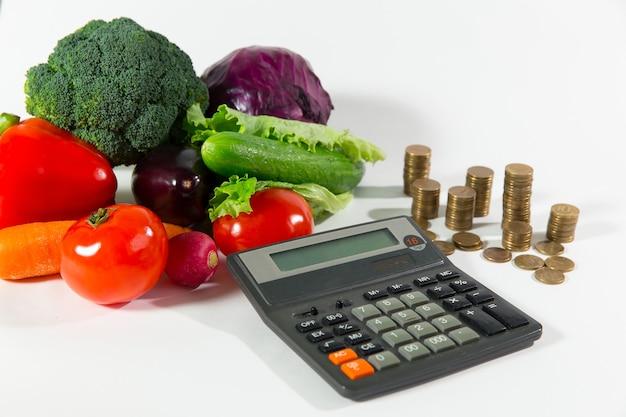 Falta de dinheiro em alimentos saudáveis, conceito de pessoas de status social de pobreza. composição de vegetais frescos maduros contra uma pilha de moedas e calculadora