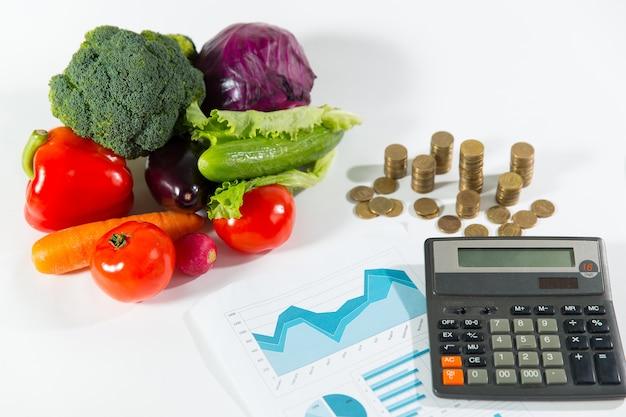 Falta de dinheiro no conceito de comida saudável. composição vegetal madura contra uma pilha de moedas