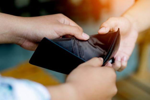Falta de finanças, falta de dinheiro, falta de renda, desemprego, mãos e bolsa, dois homens segurando a mesma bolsa. mostra falta de renda, falta de dinheiro, condições de trabalho sem dinheiro.