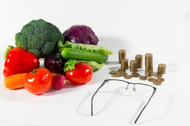 Falta de pensão em vegetais, conceito de pessoas idosas de baixo status social. composição de alimentos orgânicos maduros frescos contra uma pilha de moedas, copos e calculadora