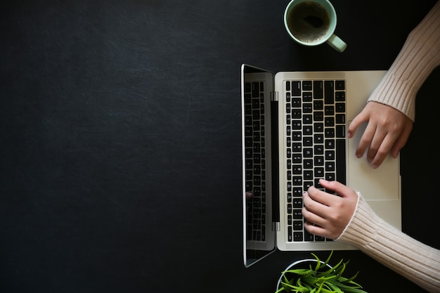 Famale trabalhando com laptop no desktop de escritório de couro escuro e espaço de cópia