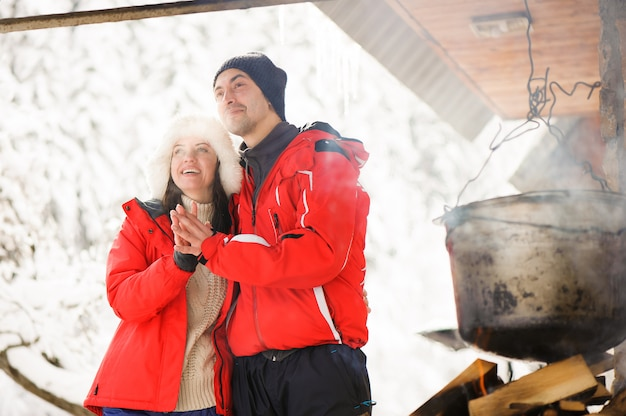 Família a cozinhar o jantar ao ar livre de inverno. fogueira, churrasco, coco.