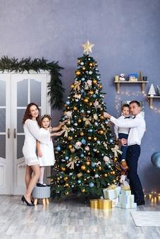 Família a decorar uma árvore de natal em casa