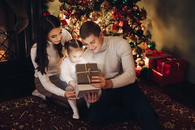 Família, abrindo o presente de natal juntos. quarto decorado para o natal.