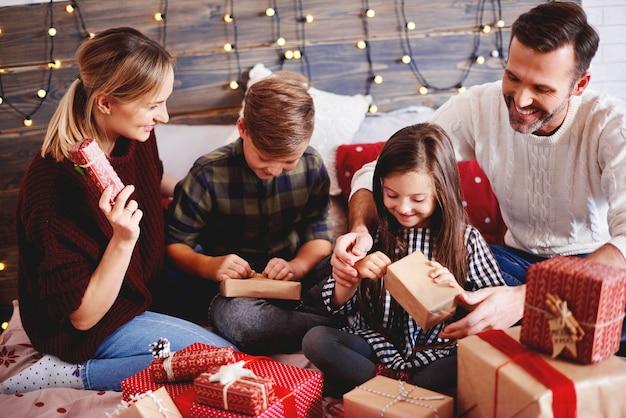 Família abrindo presentes de natal na cama