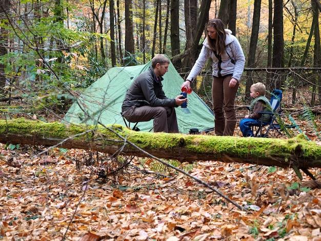 Família acampando com uma barraca em uma floresta cercada por árvores e folhas durante o outono