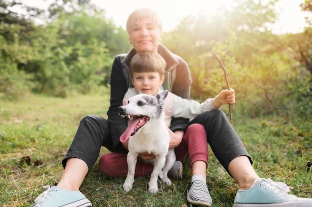 Família adorável, aproveitando o tempo lá fora com cachorro