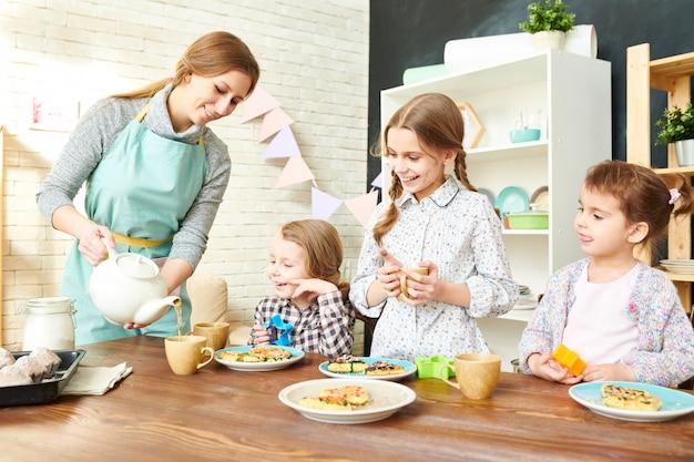 Família adorável que tem o tea party