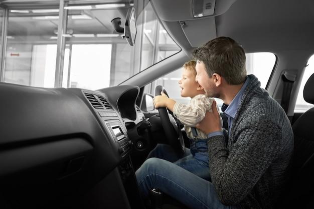 Família adorável que testa a máquina confortável no salão de automóvel