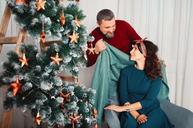 Família adulta, sentado em casa, perto de árvore de natal