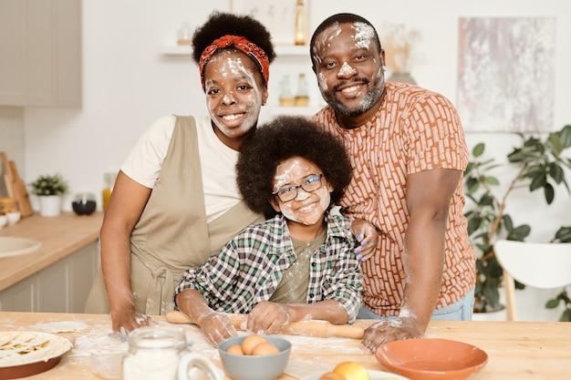 Família africana alegre e divertida de três pessoas em pé na mesa da cozinha