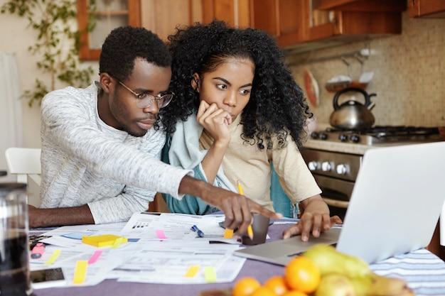 Família africana de dois, sentados à mesa na cozinha e pagando contas online usando um laptop: homem de óculos apontando o dedo indicador para a tela do caderno, explicando algo para sua esposa