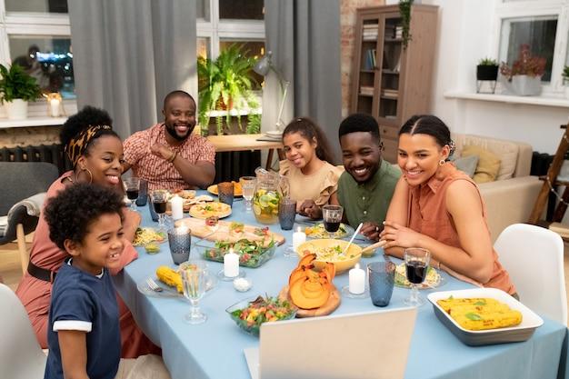 Família africana feliz composta por pai, mãe, dois filhos e filhas reunidos em uma mesa festiva conversando com seus amigos em chat de vídeo
