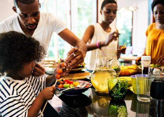 Família africana preparando churrasco na cozinha juntos