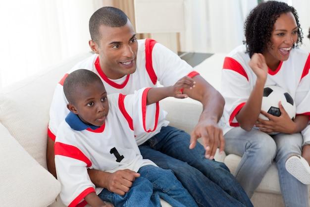Família afro-americana animada que acompanha um jogo de futebol