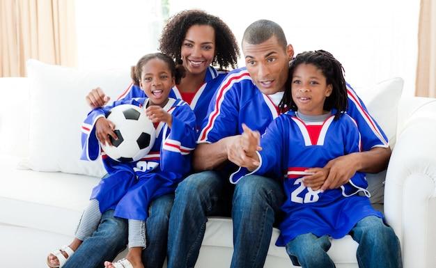 Família afro-americana assistindo a um jogo de futebol em casa