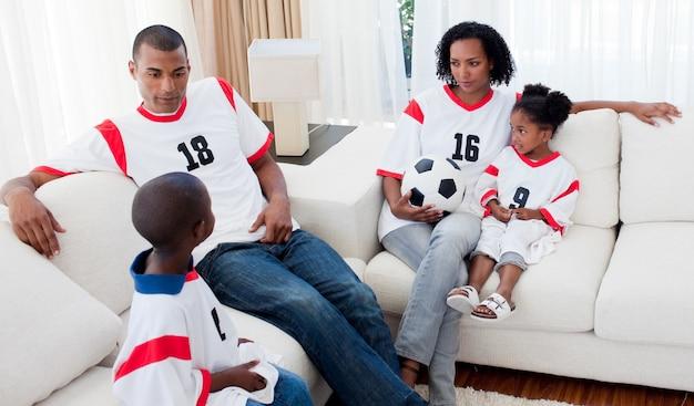 Família afro-americana assistindo um jogo de futebol