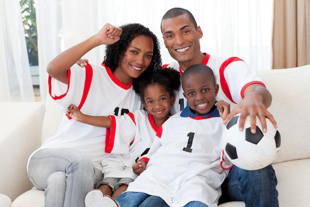 Família afro-americana comemorando um objetivo de futebol