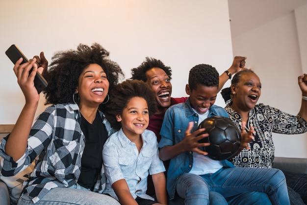 Família afro-americana de várias gerações feliz assistindo à partida de futebol na televisão na sala de estar de casa