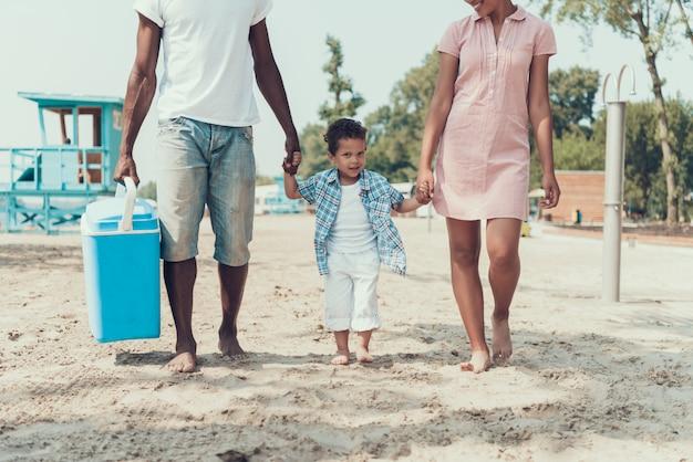 Família afro-americana está descansando na praia do rio