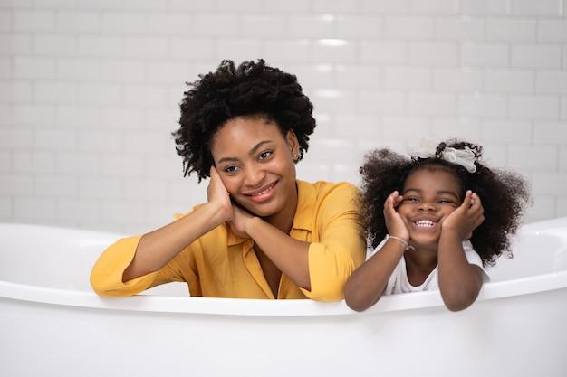 Família afro-americana, mãe feliz e filha se divertindo e brincando juntas no banheiro, parede branca backgroung