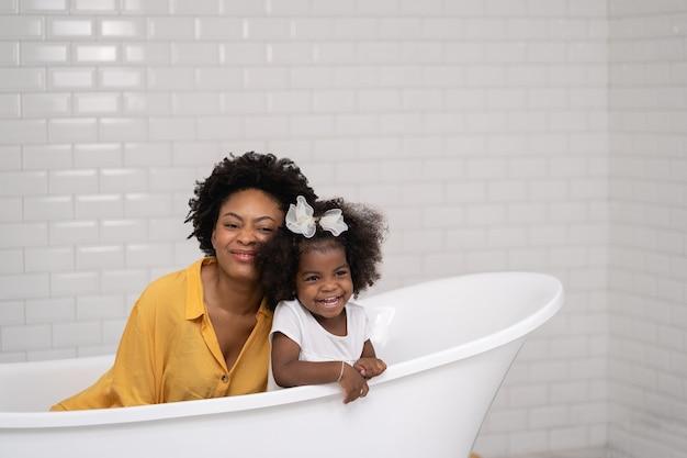 Família afro-americana, mãe feliz e filha se divertindo e brincando juntas no banheiro