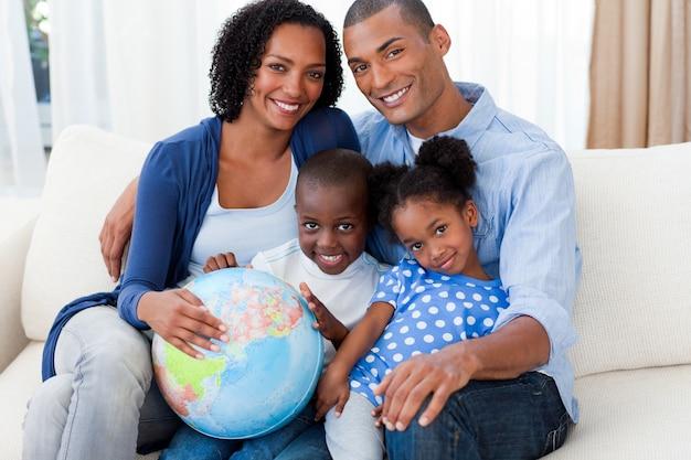 Família afro-americana que segura um globo terrestre