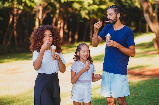 Família afro no parque tomando sorvete