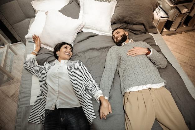 Família agradável pulando. casal alegre e radiante, conectando as mãos enquanto estava deitado na cama em uma loja de móveis